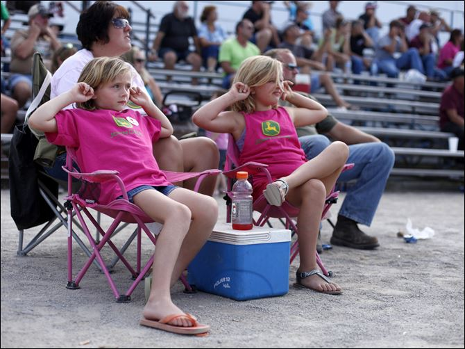 CTY TRACTORS20p Haylee and Hannah Betz of Portage, Ohio, plug their ears to muffle the noise of tractors competing at the 46th annual National Tractor Pulling Championships in Bowling Green.