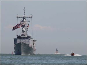 The USS De Wert receives an escort from a United States Coast Guard vessel as it makes it's way towards the mouth of the Maumee River. The Toledo Lighthouse can be seen in the background.