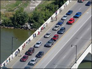 Spectators line the Martin Luther King, Jr., Bridge to watch the frigate USS De Wert make its way up the Maumee River toward downtown Toledo.