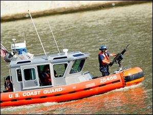 A U.S. Coast Guard boat patrols the Maumee River making sure that smaller boats don't get too close to the larger ships as they travel.E