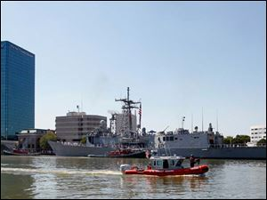 A United States Coast Guard vessel patrols the Maumee River  as the USS De Wert is tied up at One Maritime Plaza.