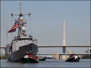 Tug boats move the USS De Wert into position as it prepares to dock.