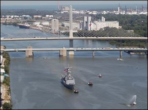 The frigate USS De Wert is pulled by tug boats up the Maumee River in Toledo, Thursday.
