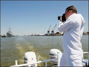 United States Navy MC1 Todd Stafford photographs the USS De Wert as it's towed into Toledo.