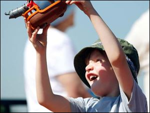 Cooper Kruse, 5, of Toledo plays with a toy boat as naval ships arrive for Navy Week Thursday.
