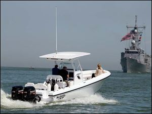 A pleasure boat heads out into Lake Erie to get a look at the USS De Wert as it powers towards Toledo.