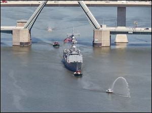 The frigate USS De Wert is pulled up the Maumee River in Toledo by a tugboat.