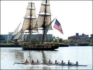 A rowing crew steers past the U.S. Brig Niagara on the Maumee River.