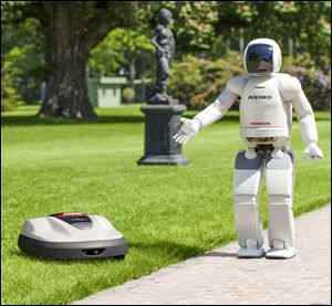 Honda Motor's Asimo, a walking talking robot, shows the company's new product lawn mower, Milmo.