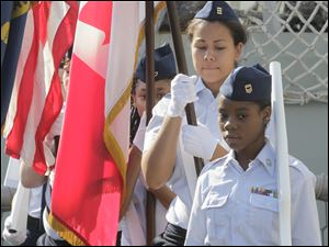 An honor guard from the the Maritime Academy of Toledo present the colors. From the front, at right, and going back: Quoliyah Byard, 14, Gabrielle Pitts, 16, and Myah Stewart, 13.