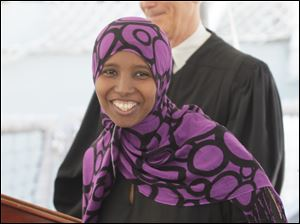 Muna Ahmed Abdi, an American from Somalia, with her certificate of citizenship. 24 people become U.S. citizens in a ceremony hosted by U.S federal judge James G. Carr and U.S. Navy Cdr. Joseph C. Thomas aboard the USS DeWert in Toledo, Ohio on August 24, 2012.
