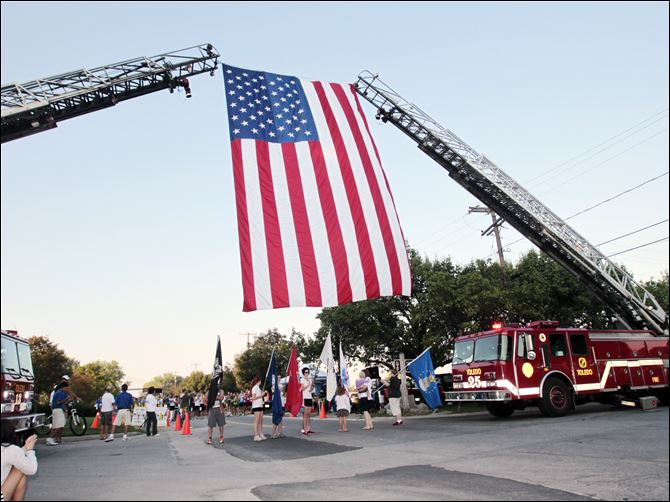 Two Toledo Fire Department ladder trucks provide an archway Two Toledo Fire Department ladder trucks provide an archway to mark the start line of the 5K run and support an American flag flown in honor of Navy Week festivities in Toledo.