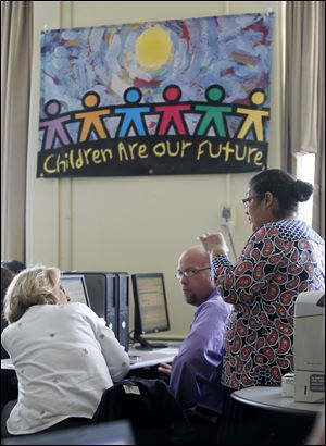 Connie Solano, right, a representative of the system's developer, helps TPS' Glenna Feller and John Krajeski.
