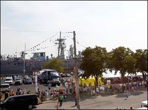 The line for visitors to board the USS De Wert extends all the way down Water Street past the factories.