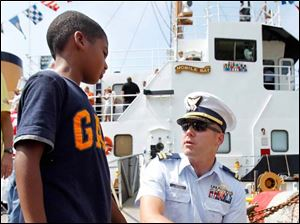 Navy Lt. Harold Kiffer, Chief Executive Officer, answers questions DeJuan Hood, 7, of Toledo, while on a tour of the USCGC Mobile Bay.