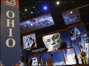 Behind the Ohio state delegate sign, pictures of Ohio native Neil Armstrong, the first man to walk on the moon, are displayed on the main stage the Republican National Convention in Tampa.