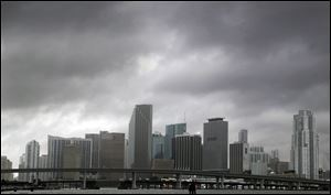 Heavy storm clouds hover over the skyline of downtown Miami as Tropical Storm Isaac's weather bands reach the shore. Forecasters warning it could grow into a dangerous Category 2 hurricane as it nears the northern Gulf Coast.