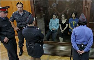 Nadezhda Tolokonnikova, right, Yekaterina Samutsevich, left, and Maria Alekhina, center, members of feminist punk group Pussy Riot seen behind a glass wall at a court in Moscow, Russia, on Aug. 17.