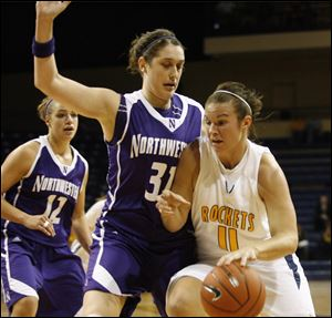 University of Toledo's Allie Clifton dribbles around the defense of Northwestern's  Dannielle Diamant, left #31, and Allison Mocchi, back #12, during the  first half of the women's basketball home opener against Northwestern on November 13, 2009.