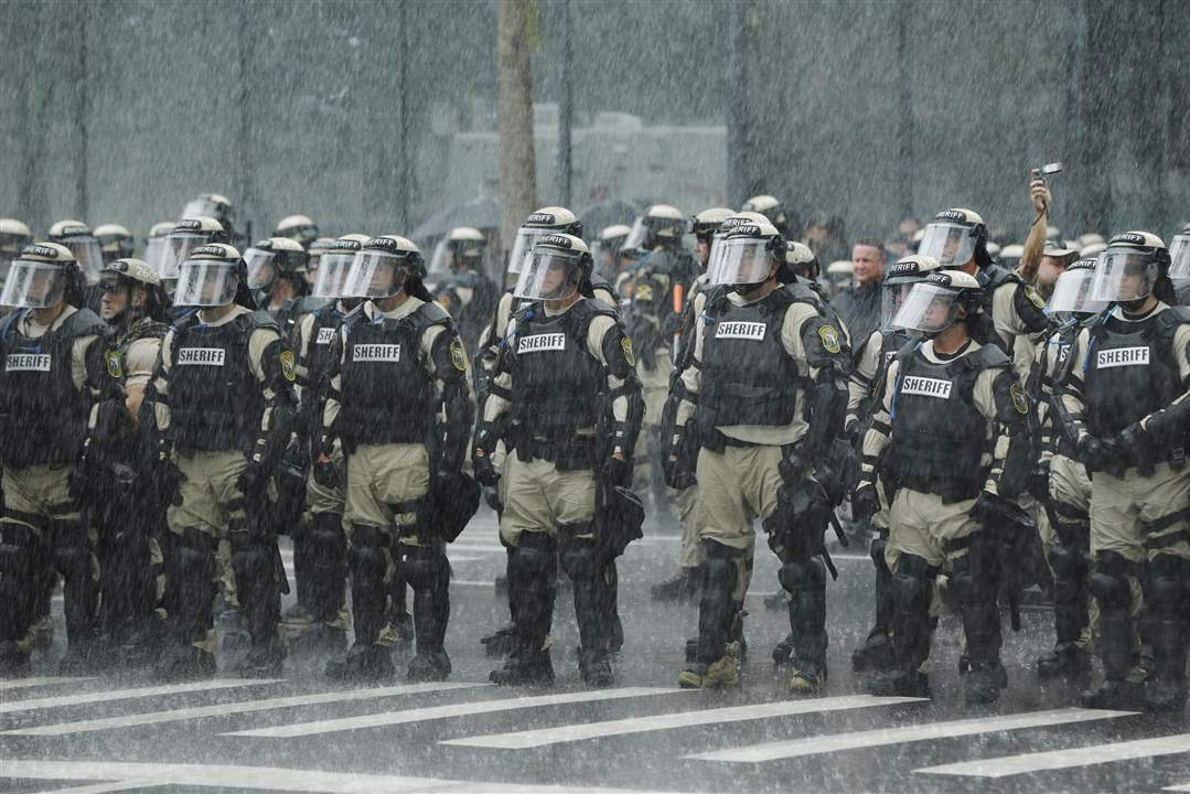 APTOPIX-Republican-Convention-Protests-officers-downpour