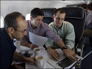 Republican vice presidential candidate Paul Ryan, center,  R-Wis., works on the speech he will deliver at the Republican National Convention, with senior adviser Dan Senor, left, and senior aid Conor Sweeney during the campaign charter flight from Wisconsin to Tampa.