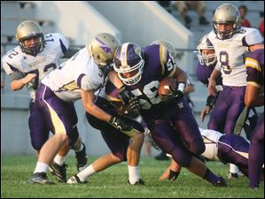 Maumee Lucas Junga (5) and Alex Schultz (31) bring down a Waite ball carrier (58).