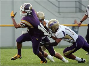 Waite's Tyler Slawski (10) is stopped by Maumee's Exavier Ealy (14).