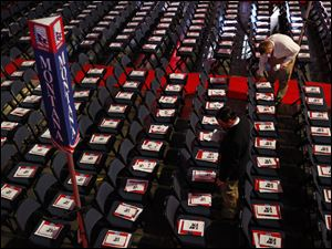 A volunteer places pamphlets on chairs in Montana's delegation seating area.