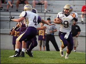 Maumee quarterback Steve Duby (9) runs with the ball against Waite.