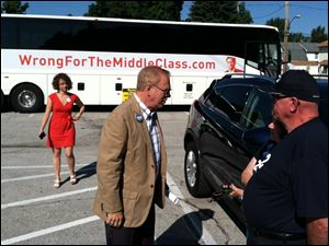 Ted Strickland, center, speaks to people at the East Toledo stop of his anti-Mitt Romney bus tour Tuesday.