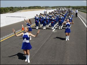 Anthony Wayne High School majorettes Lindsey Alleman, front, Katie Music, back left, and Sara Dick, right, perform with the Anthony Wayne High School Marching Generals during a ribbon cutting ceremony for U.S. 24.
