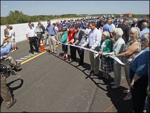Spectators take turns posing with a ceremonial ribbon during a ceremony in Monclova Township near Waterville to open Ohio's final portion of the new alignment of U.S. 24.