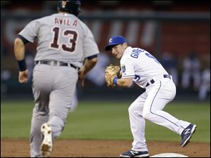 Kansas City Royals second baseman Johnny Giavotella, right, prepares to throw to first for the double play hit into by Detroit Tigers' Austin Jackson after forcing Alex Avila (13) out at second during the third inning in Kansas City.