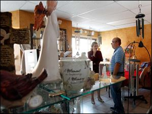 Jason Dettrow, left, co-owner of the The Secret Garden Floral & Gifts on West Tully Street in Convoy shows Ohio congressional candidate Angela Zimmann the expanded area of his shop.