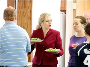 Ohio congressional candidate Angela Zimmann, center, serves a free senior meal at the Trinity Evangelical Lutheran Church.