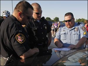 Wood County Sheriff deputies Jamie Webb and Chris Klewer coordinate with Perrysburg Police Sgt. Brian Gregg during an event this summer in Perrysburg.