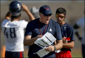 University of Arizona football coach Rich Rodriguez calling out to his players as they run drills during team practice in Sierra Vista, Ariz.