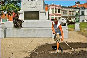 Dan Koerper of Mohawk Nursery prepares topsoil near the statue of Gen. William Harvey Gibson. He was part of a four-men crew who worked Thursday. Underground irrigation is to be completed today.