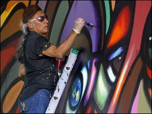 Mario Torero, of San Diego, works on a mural on the viaduct below I-75 on Broadway in 2011.