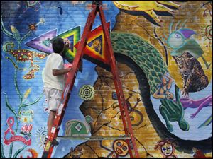 Bob Garcia, an Organization of Latino Artists member, touches up a mural on the building at the corner of Jervis and Broadway in Toledo. The colorful painting is a collaboration between other art groups, and is one of 16 along Broadway.