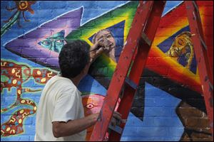 Bob Garcia, an Organization of Latino Artists member, touches up a mural on the building at the corner of Jervis and Broadway in Toledo.