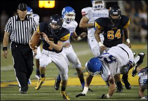 Whitmer quarterback Nick Holley darts up the middle for one of his two second-half touchdowns.