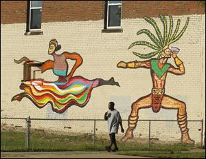 A man walks past images of dancers painted this summer by BGSU students.