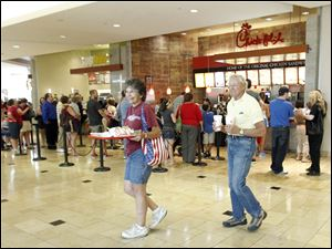 Arline and Forest Sabin carry food from Chick-fil-A in Westfield Franklin Park in support of Dan Cathy, the chain's owner, in August.