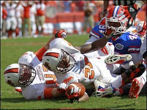Bowling Green running back John Pettigrew dives past Florida linebacker Darrin Kitchens for a one-yard touchdown run in the first quarter. He had 38 yards on eight attempts in the loss.