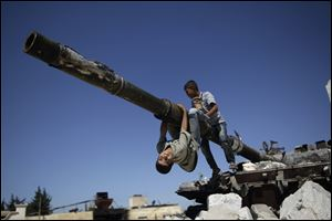 A  boy looks back while he and another boy play on a Syrian military tank, destroyed during fighti