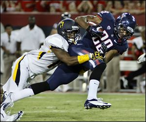 Arizona's Austin Hill (29) tries to break the tackle of Toledo's Cheatham Norrils, left, during the first half of an NCAA college football game at Arizona Stadium in Tucson, Ariz.