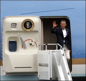 President Obama waves from the door of Air Force One as he lands Sunday at Toledo Express Airport.