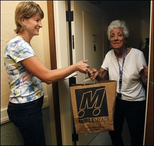 Annette Clark, director of Family Service of Northwest Ohio, delivers a meal to Barbara Lambert at the Renaissance Senior Apartments in Toledo. Mobile Meals is looking for at least 50 volunteers.