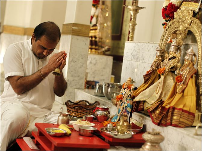 CTY Asian Community29p Pandit Anantkumar B. Dixit prays with his congregation at the Hindu Temple in Toledo, formed in the early 1980s.